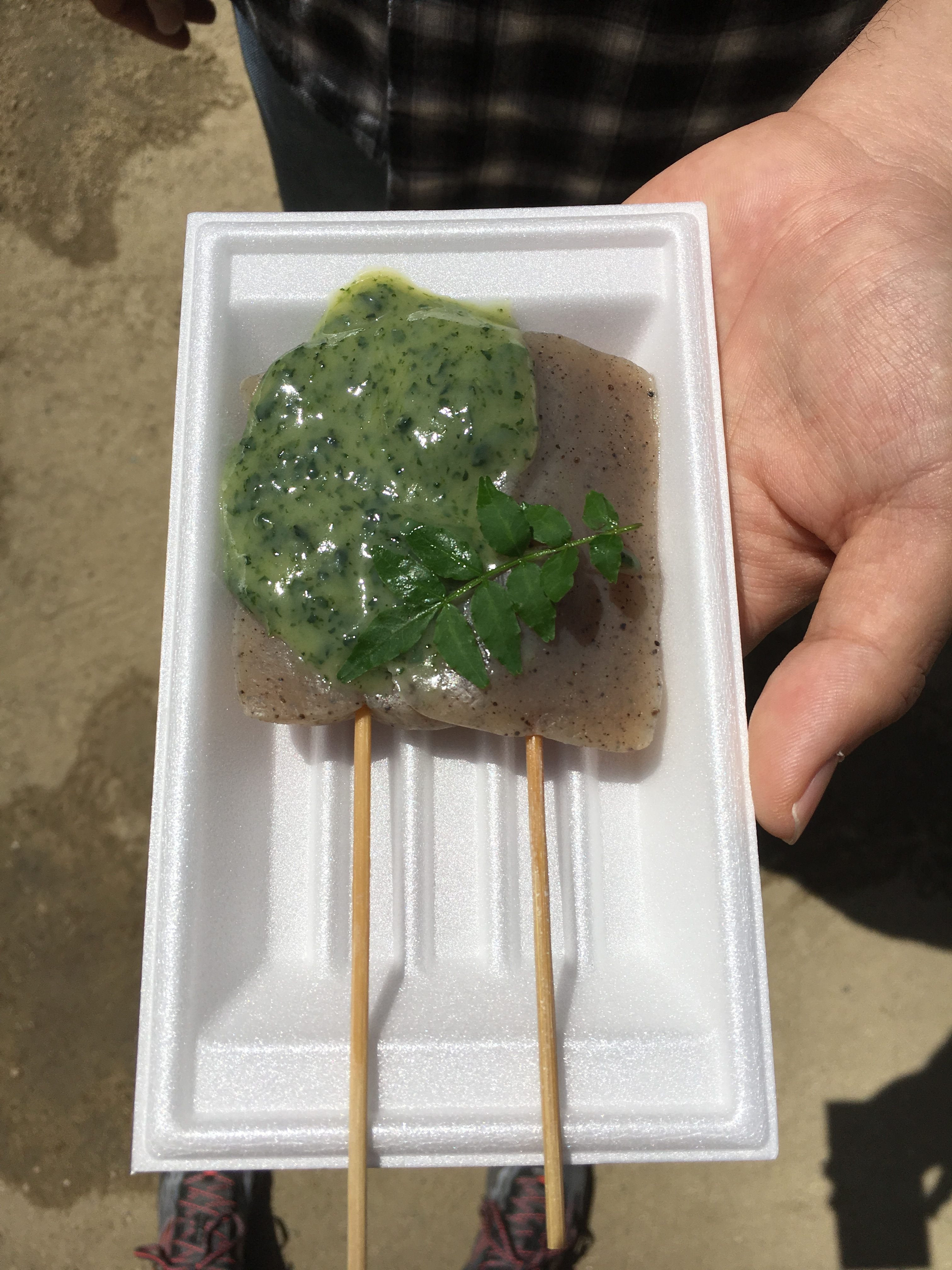 two pieces of of konyaku covered in green sauce