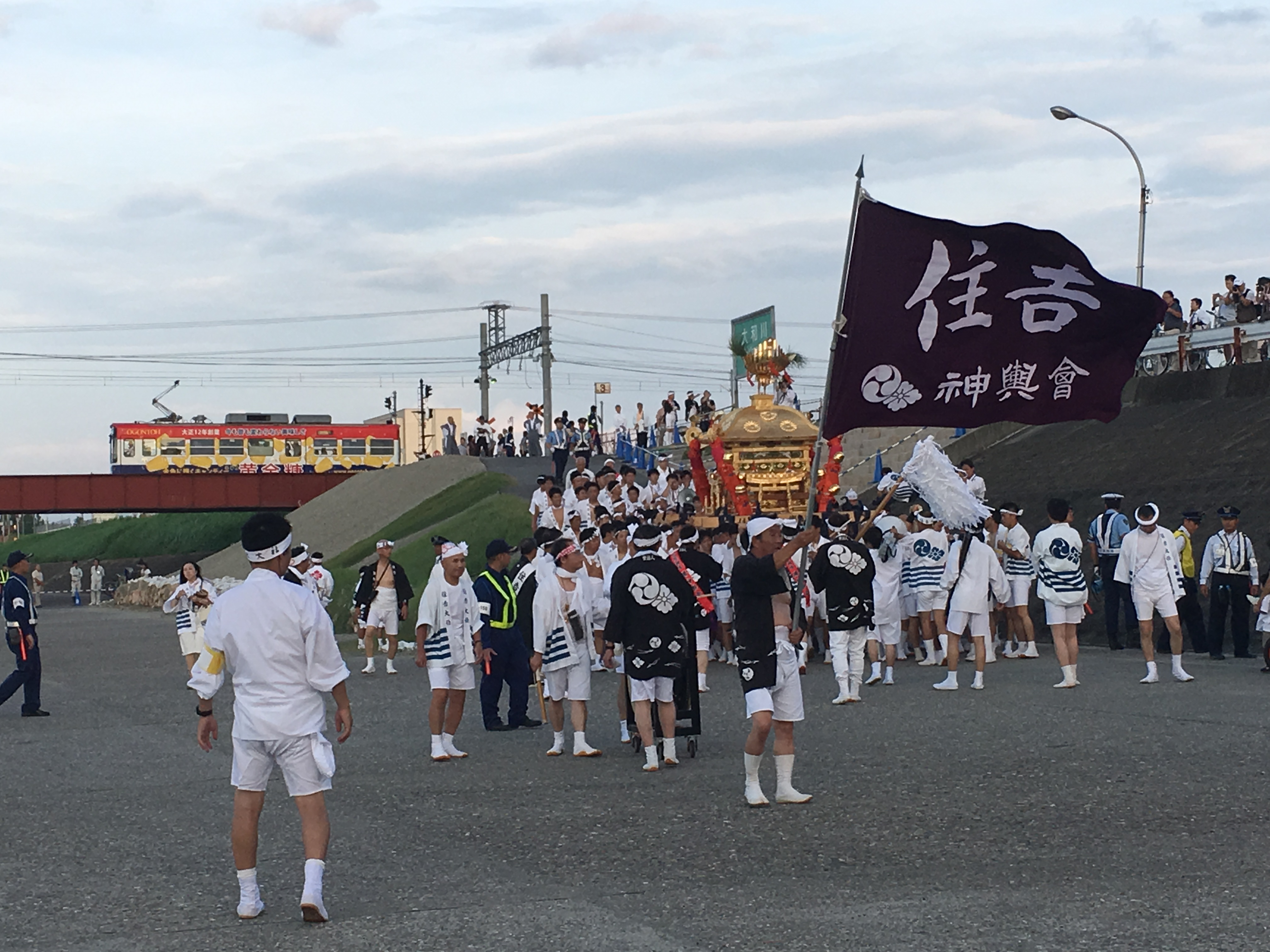 Sumiyoshi Matsuri participants meeting along the river side as a train passes in the distance