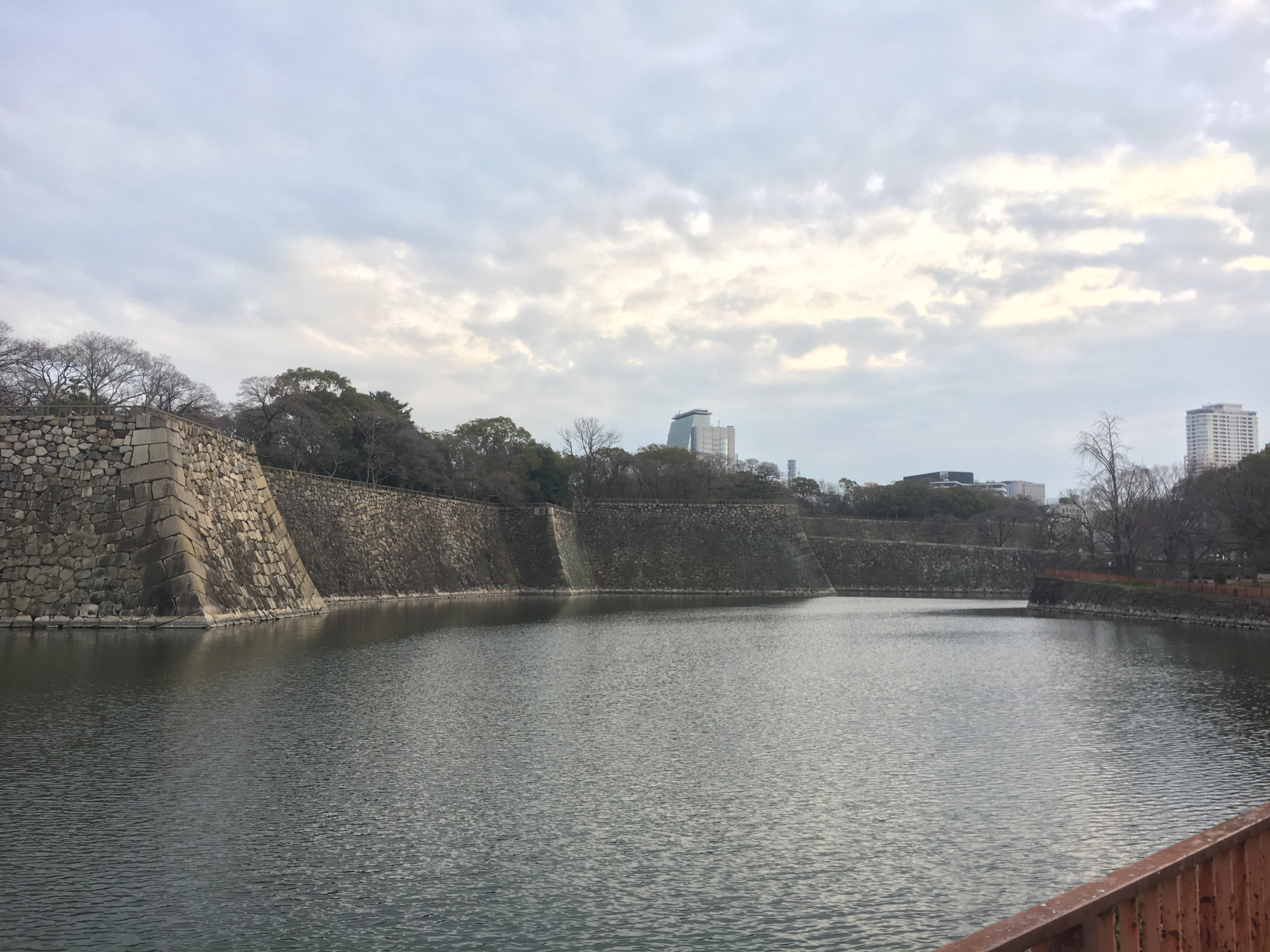 large tokugawa period stone castle walls and moat on a cloudy day