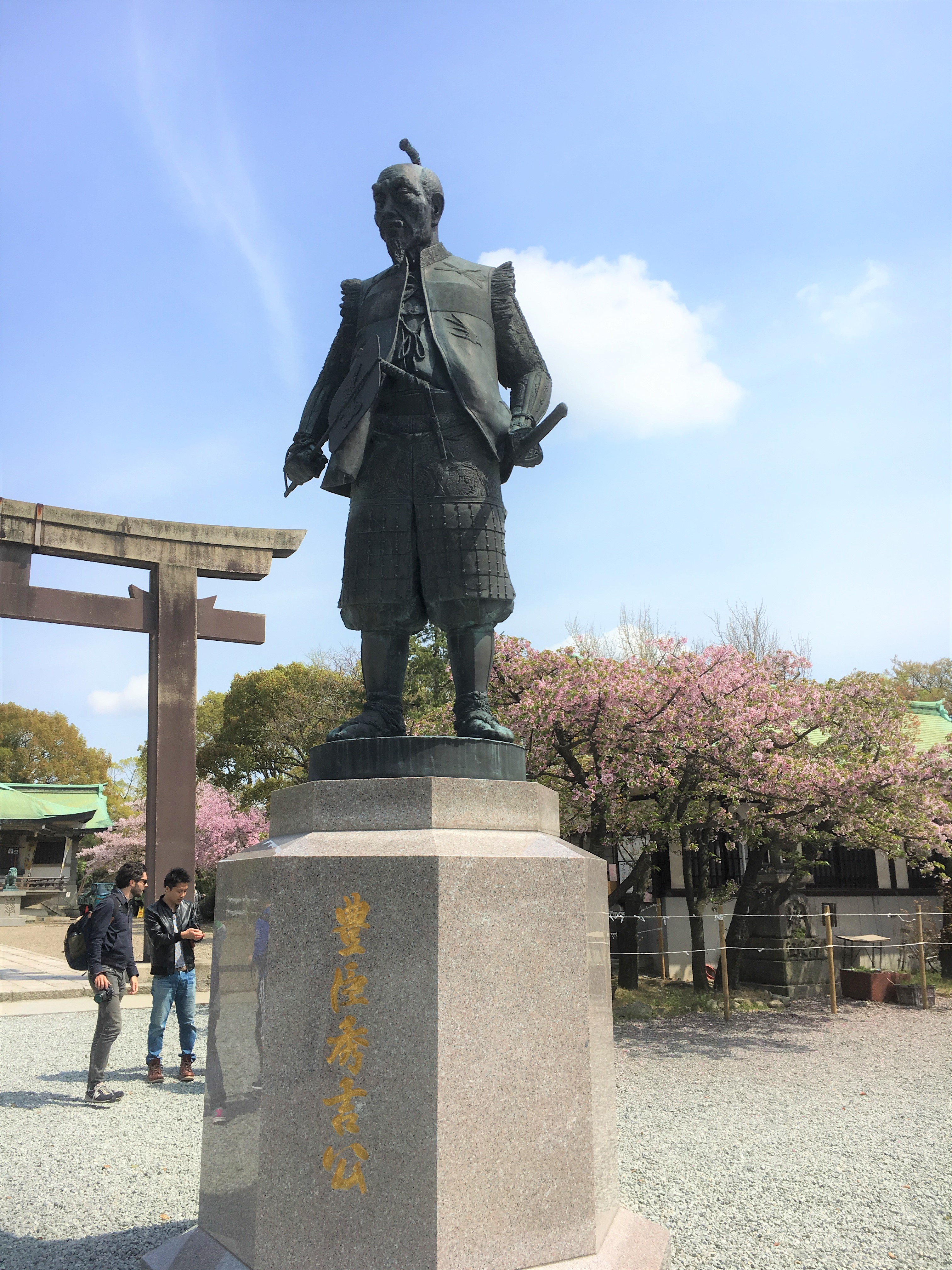 statue of hideyoshi with cherry blossoms in background