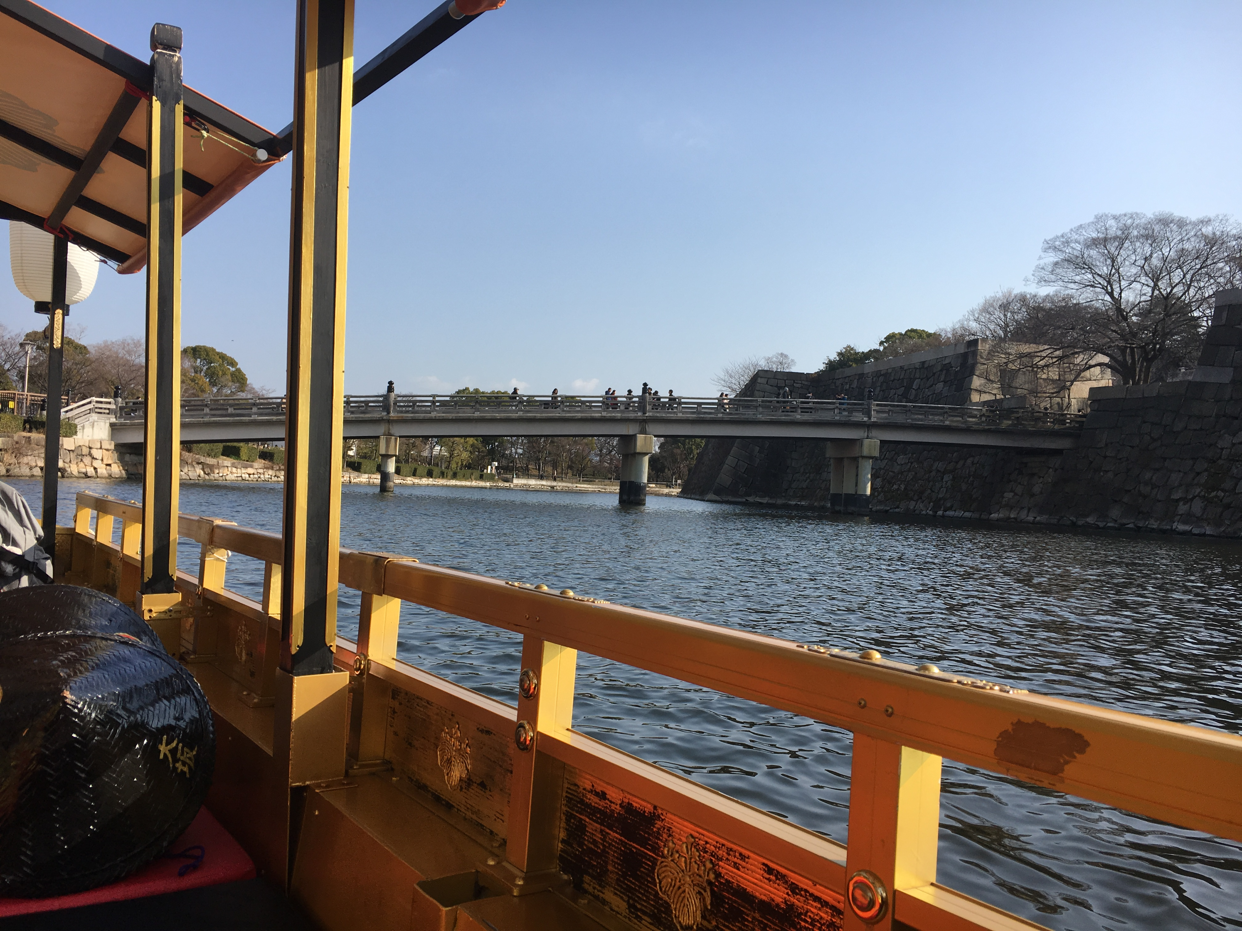 small boat with golden roof in moat of Osaka Castle