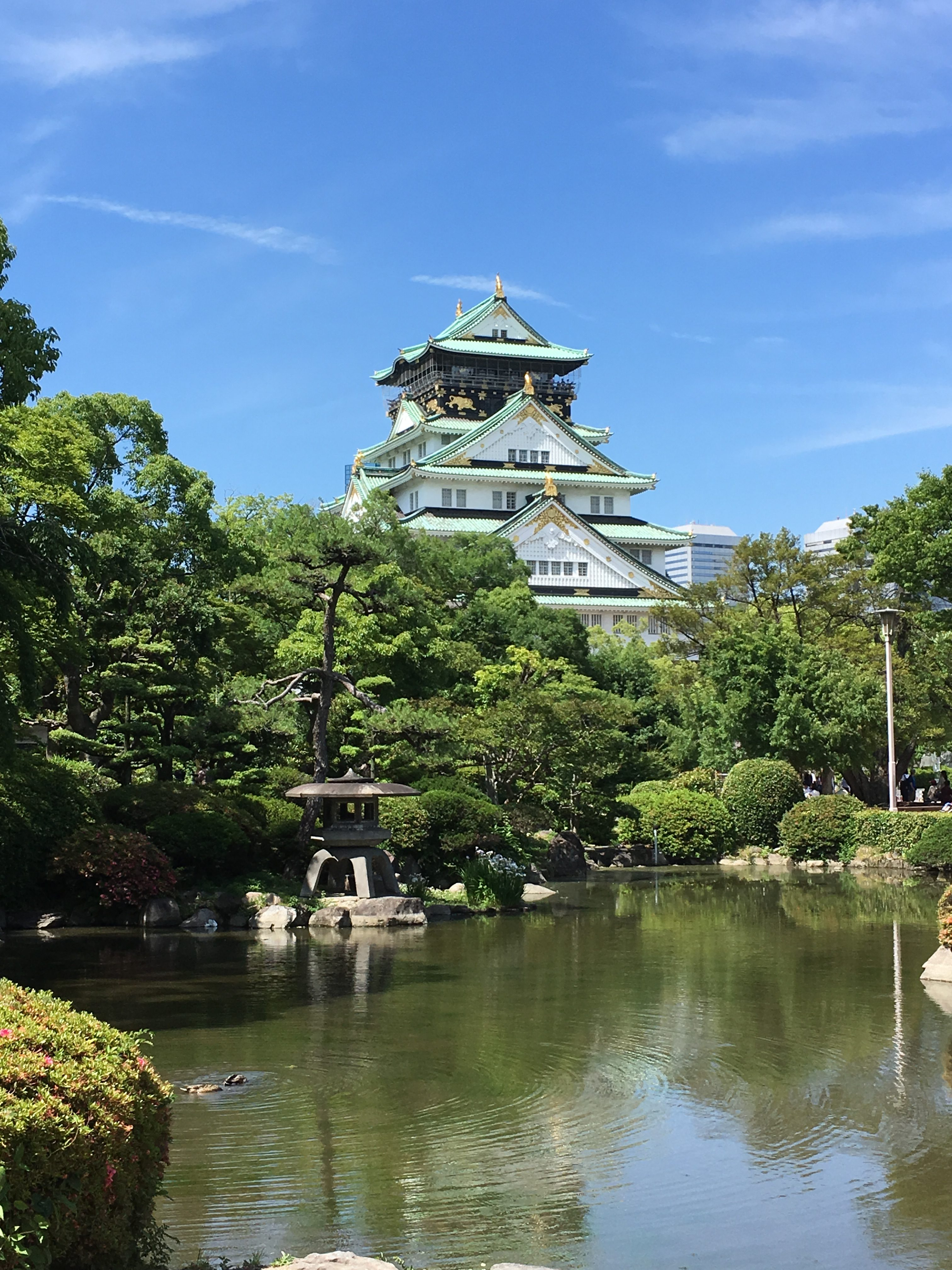 view of Osaka Castle with pond in foreground and Japanese style garden