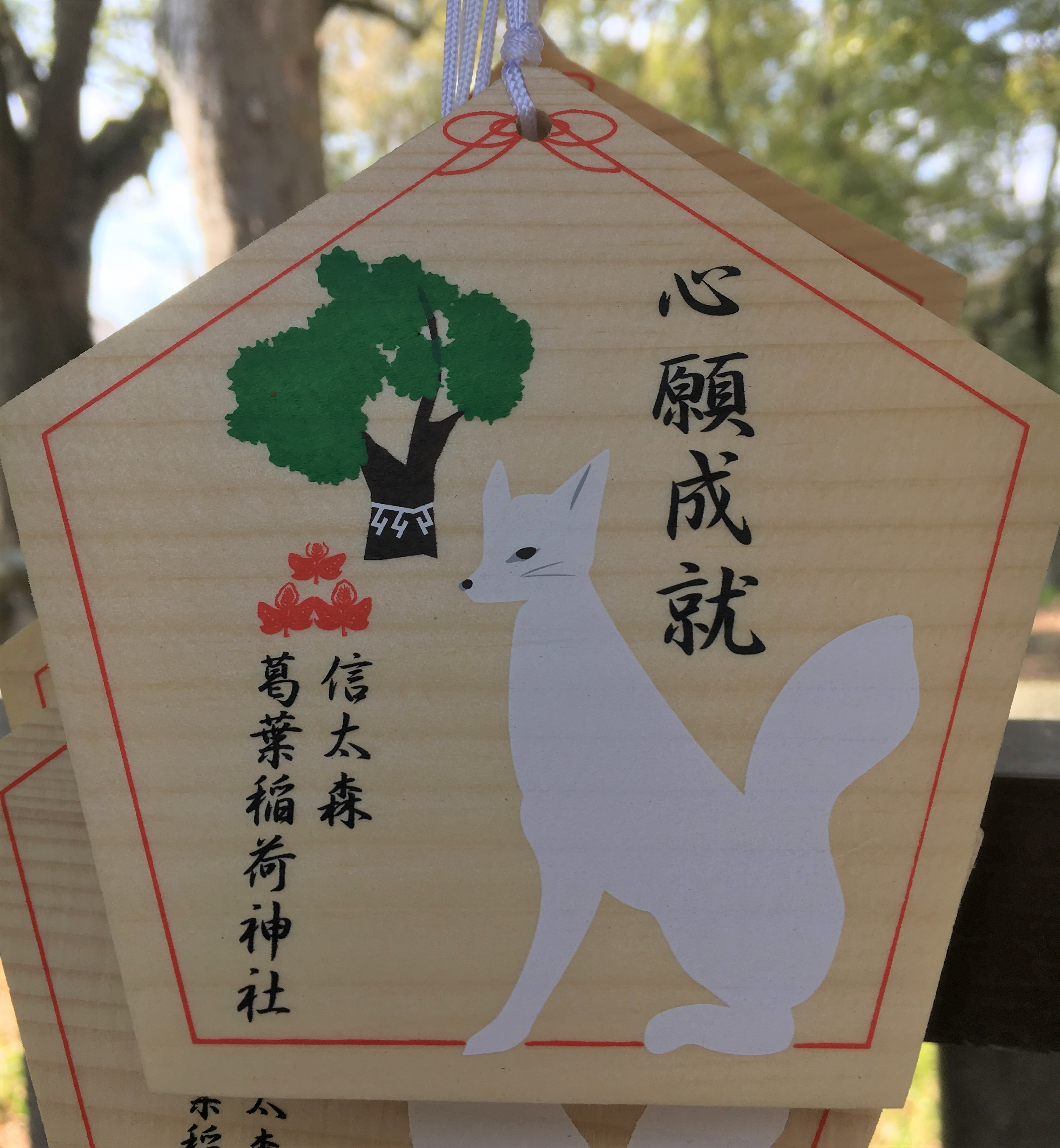 wooden ema with white fox and tree
