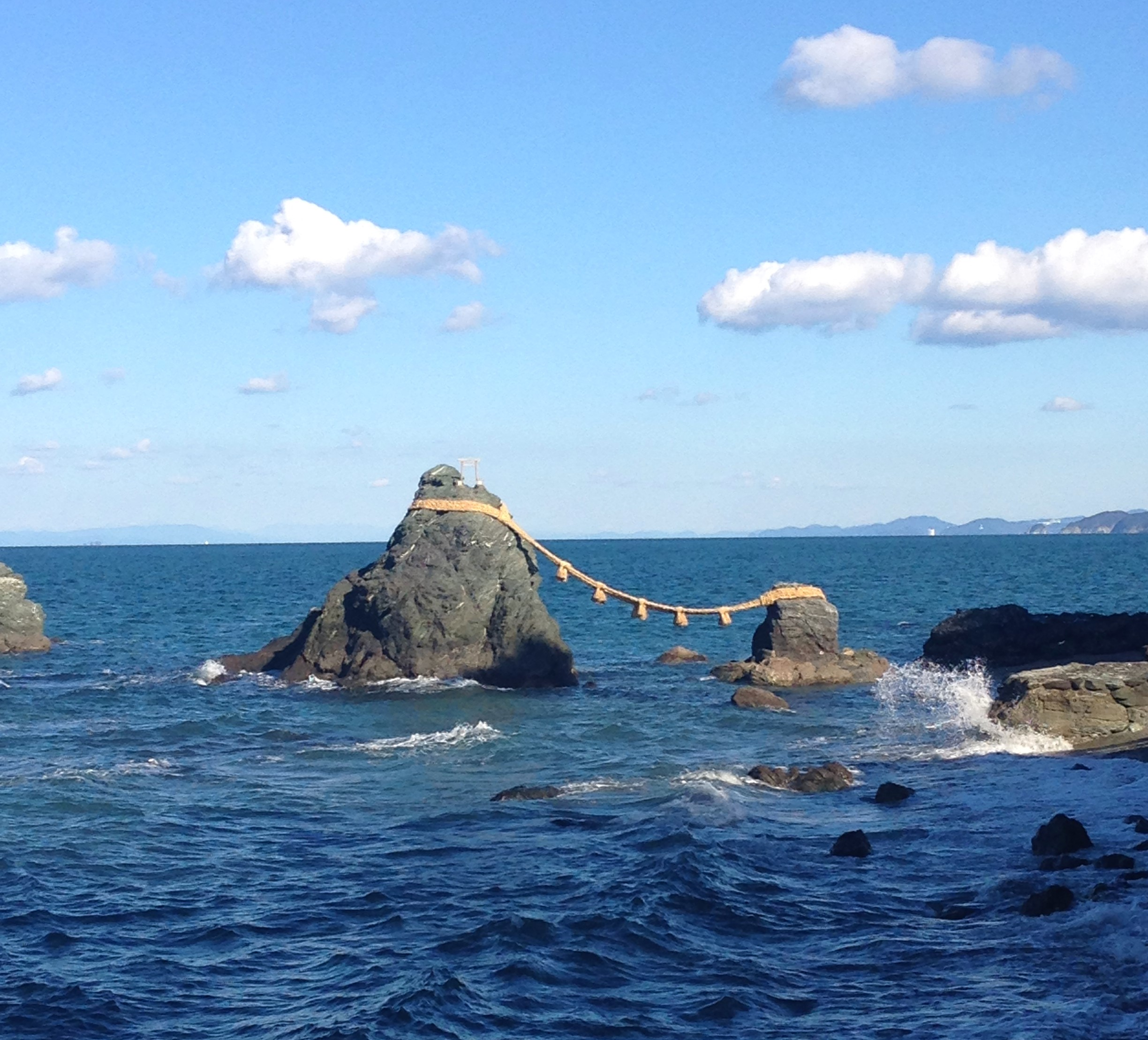 two large rocks connected by a long rope and a shrine on the taller rock in the blue sea