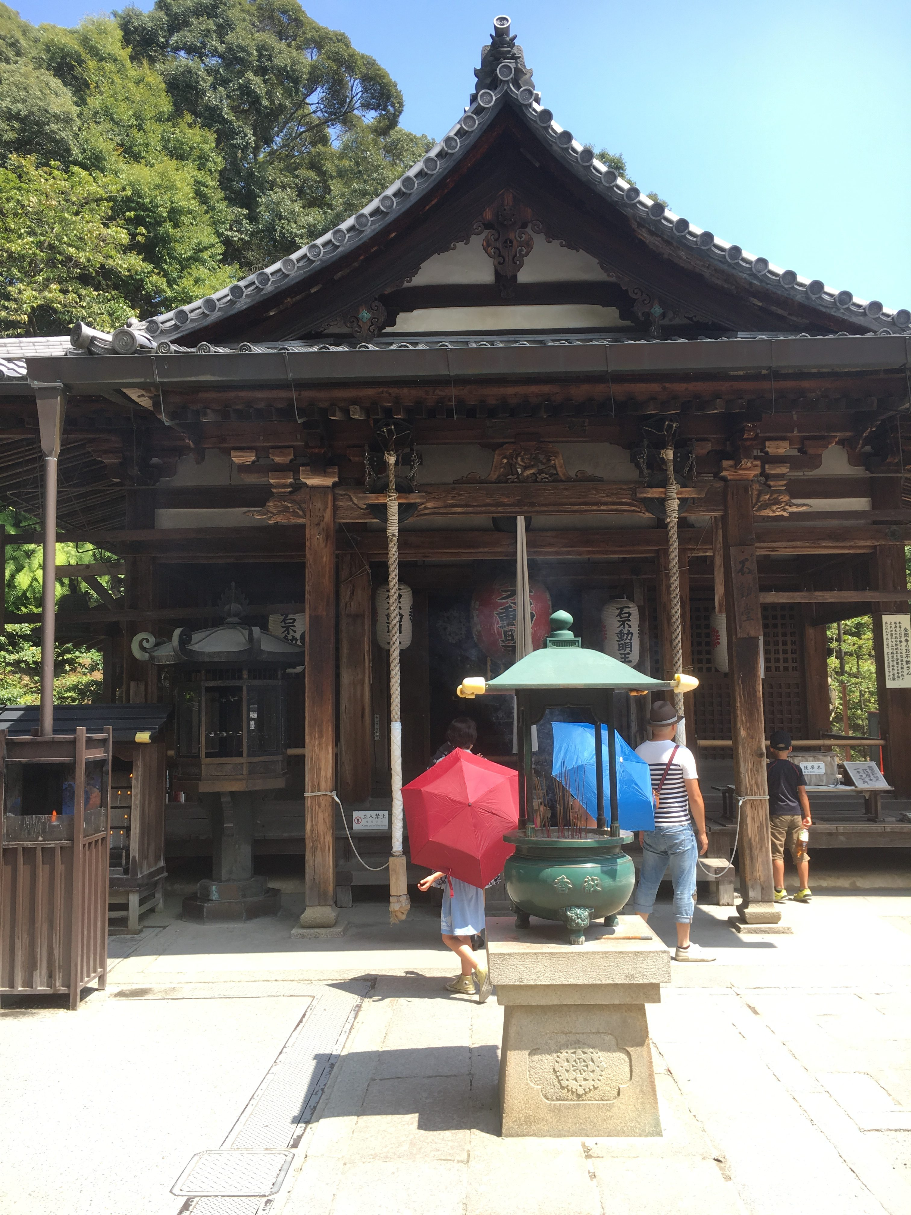 Old Japanese style temple with pot of incense and tourists