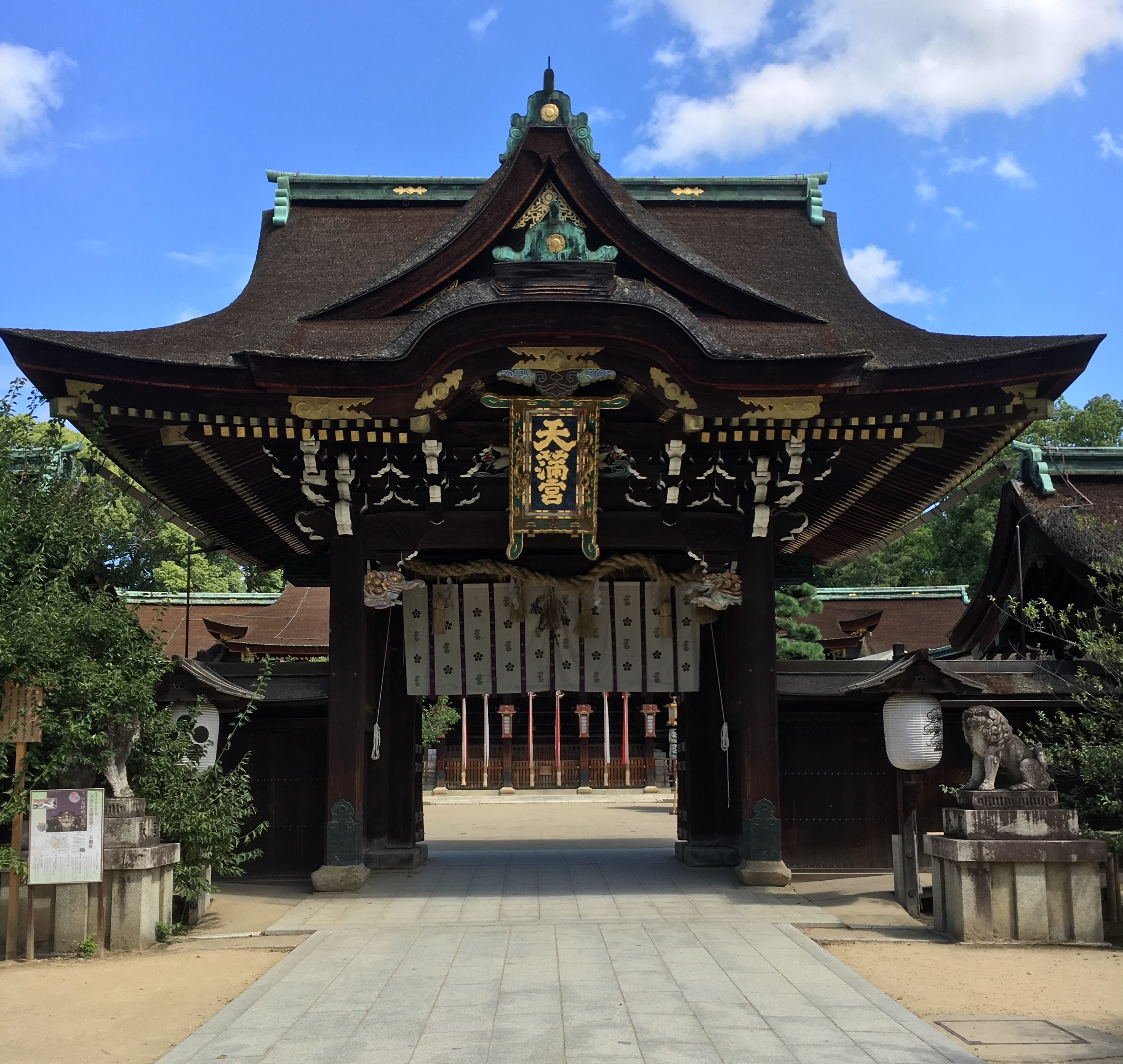 iconic gate at kitano tenmangu shrine with large name plate in gold lettering