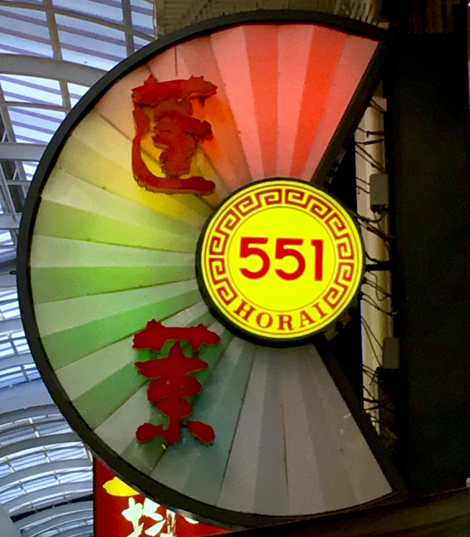 Half circle shaped rainbow colored neon sign for a restaurant and the numbers 551