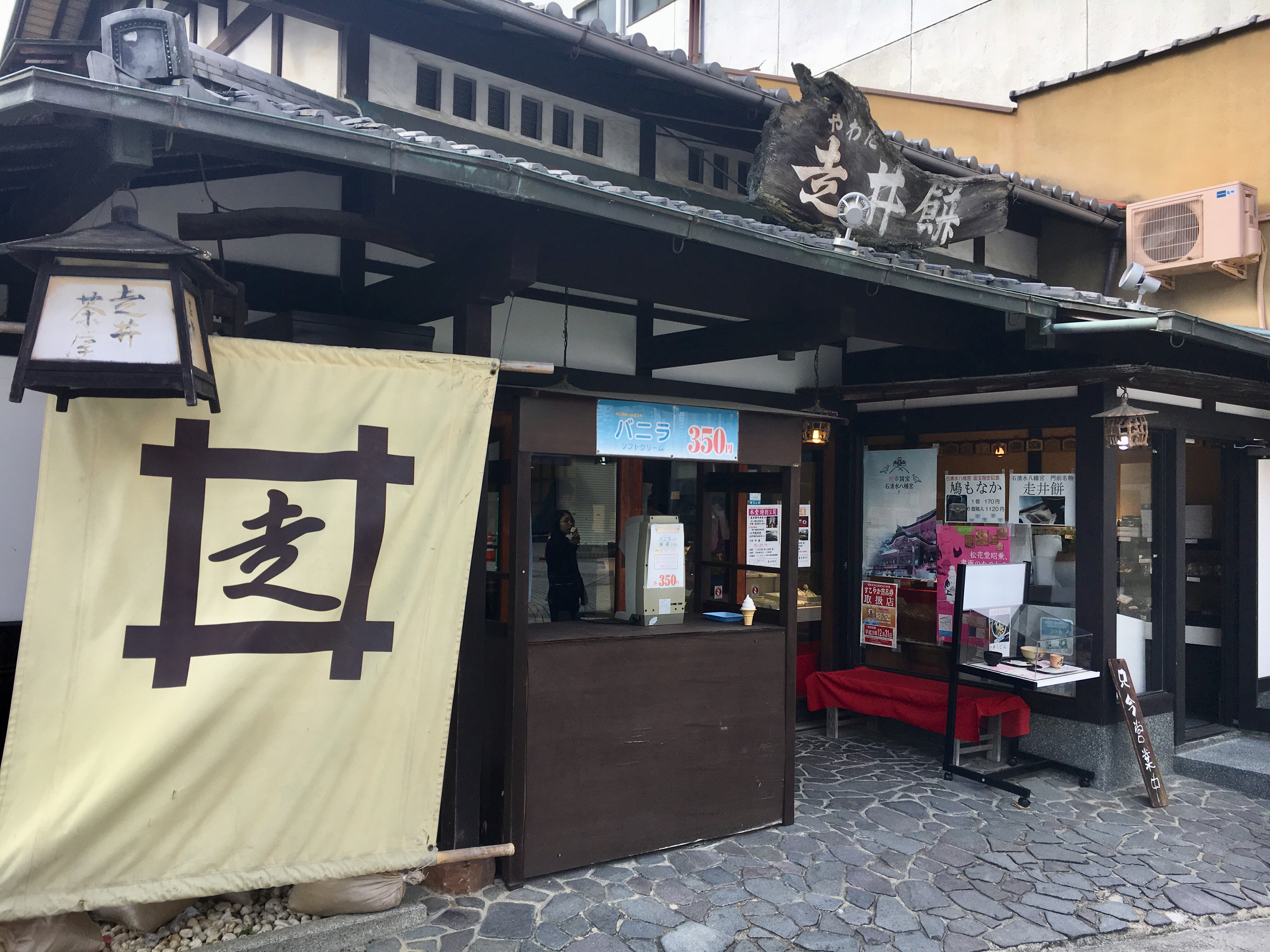 old fashioned Japanese restaurant with dark wood fixtures and large cloth sign