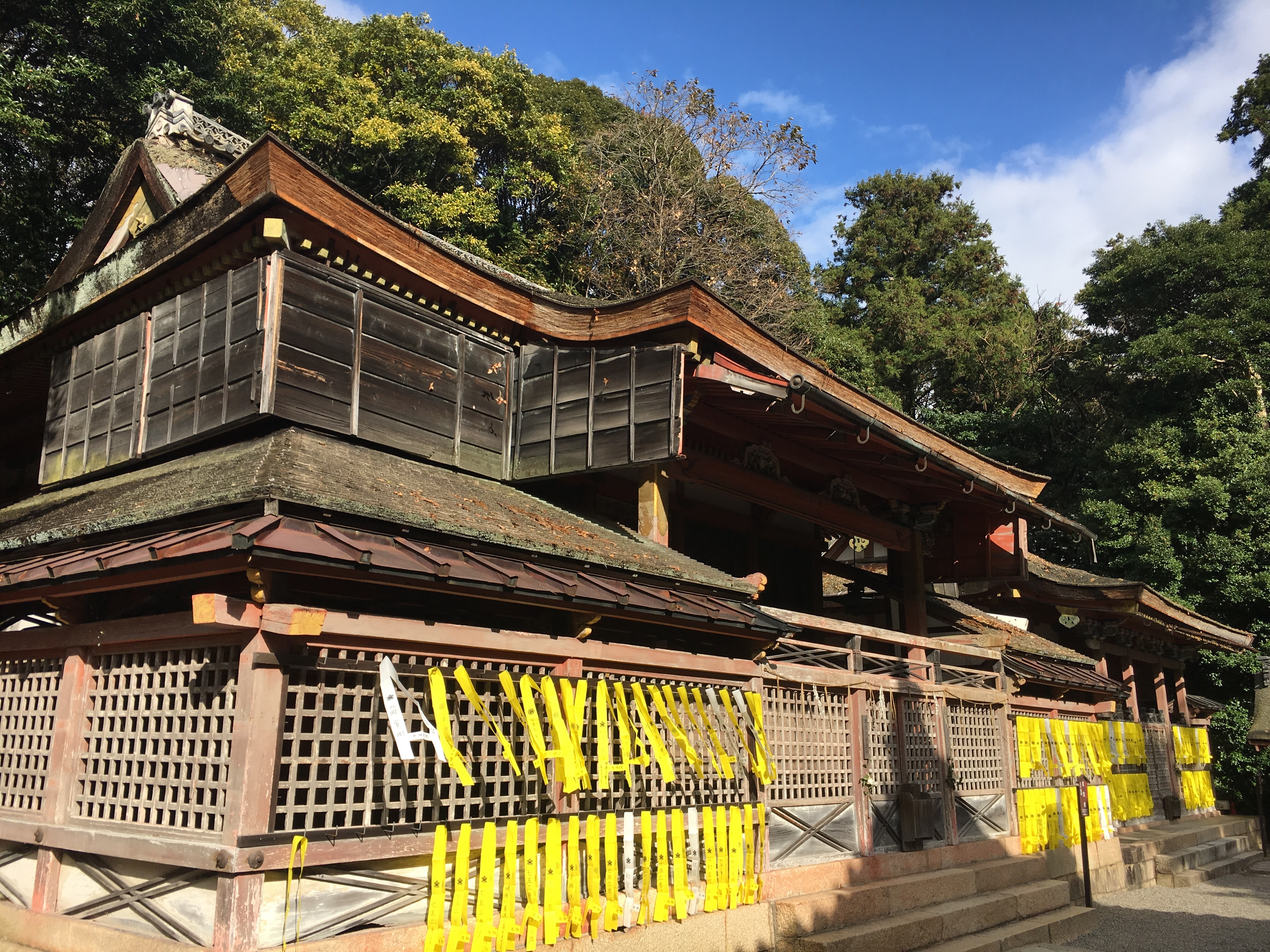 large wooden shinto shrine covered in yellow strips of fabric