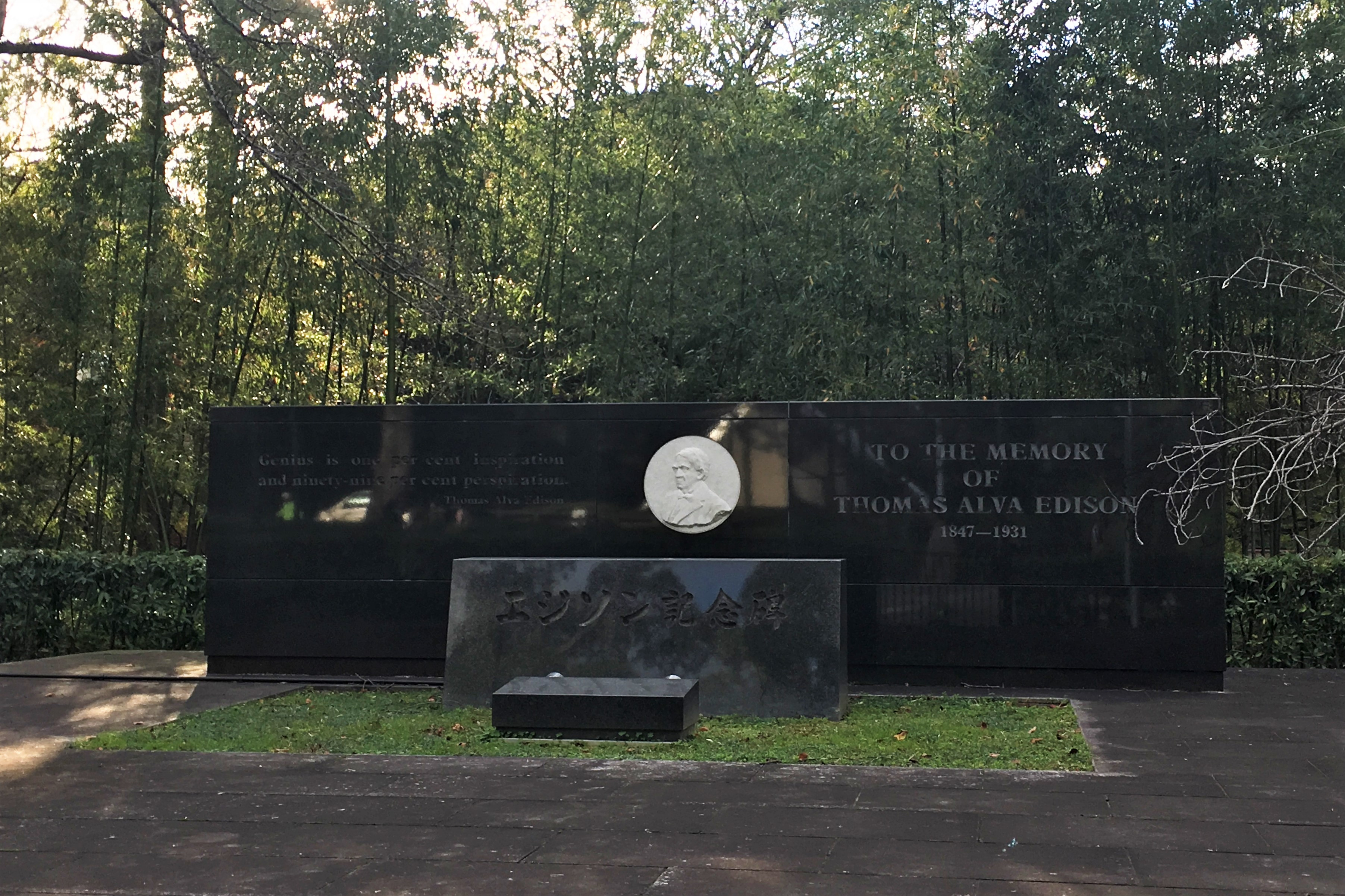 large black memorial to Thomas Edison surrounded by bamboo