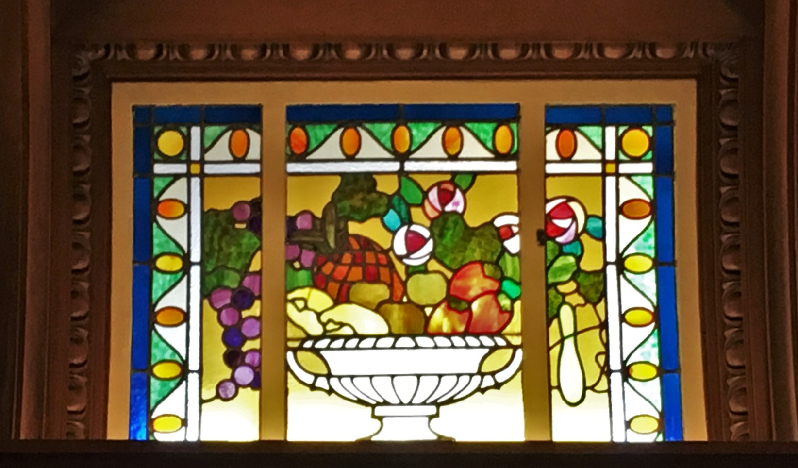 stained glass pane of a bowl of fruit warm backlight