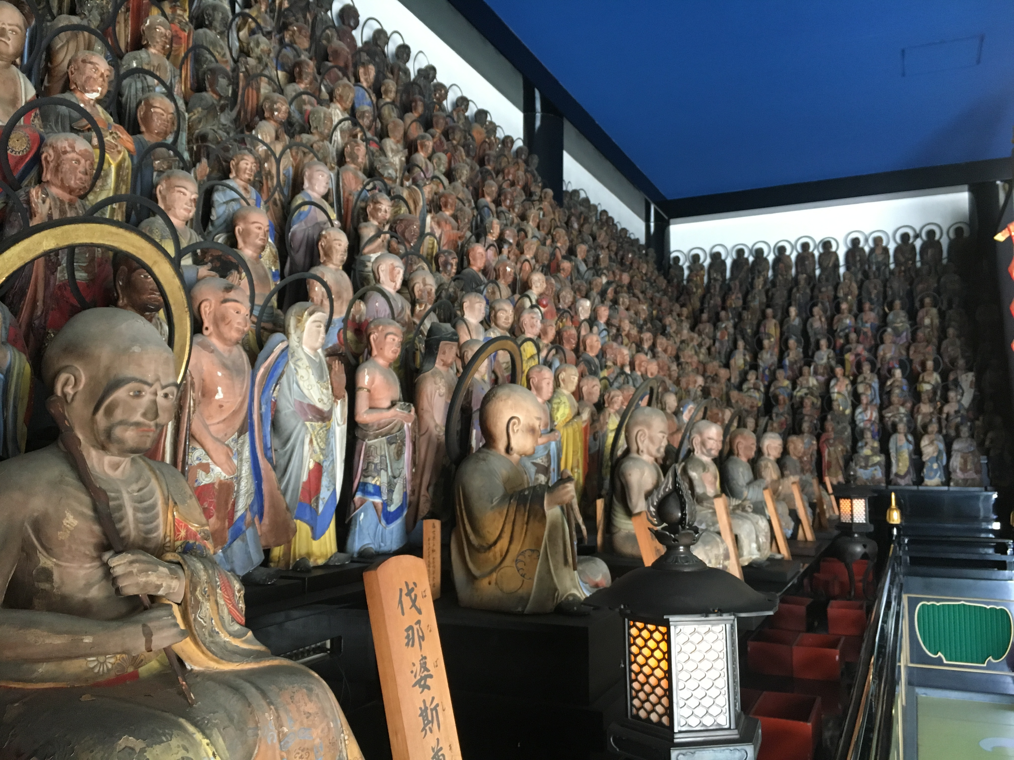 rows of old statues of Buddhist priest and practitioners