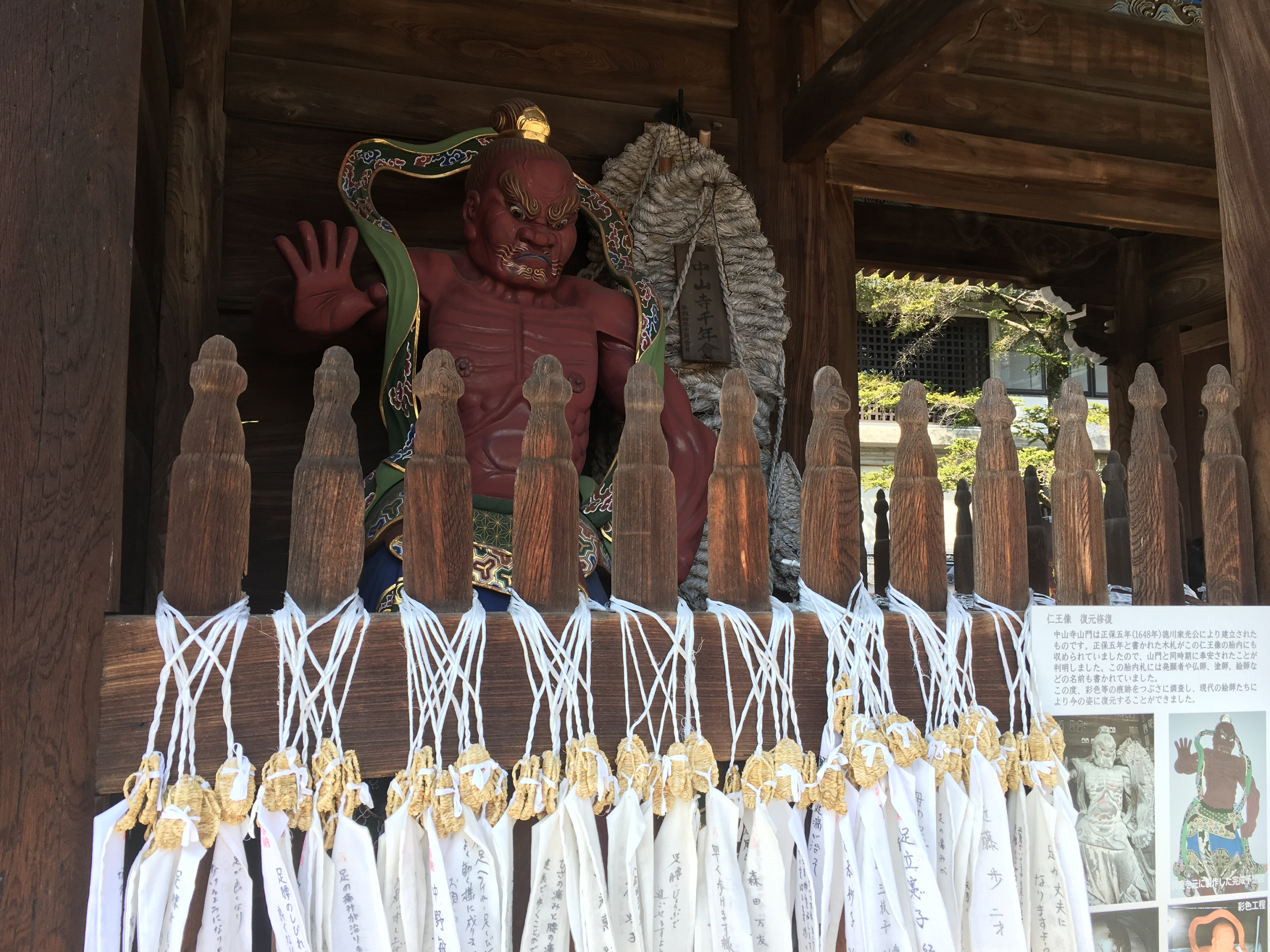 fearsome red statue guards Nakayama-dera entrance covered in small straw sandals