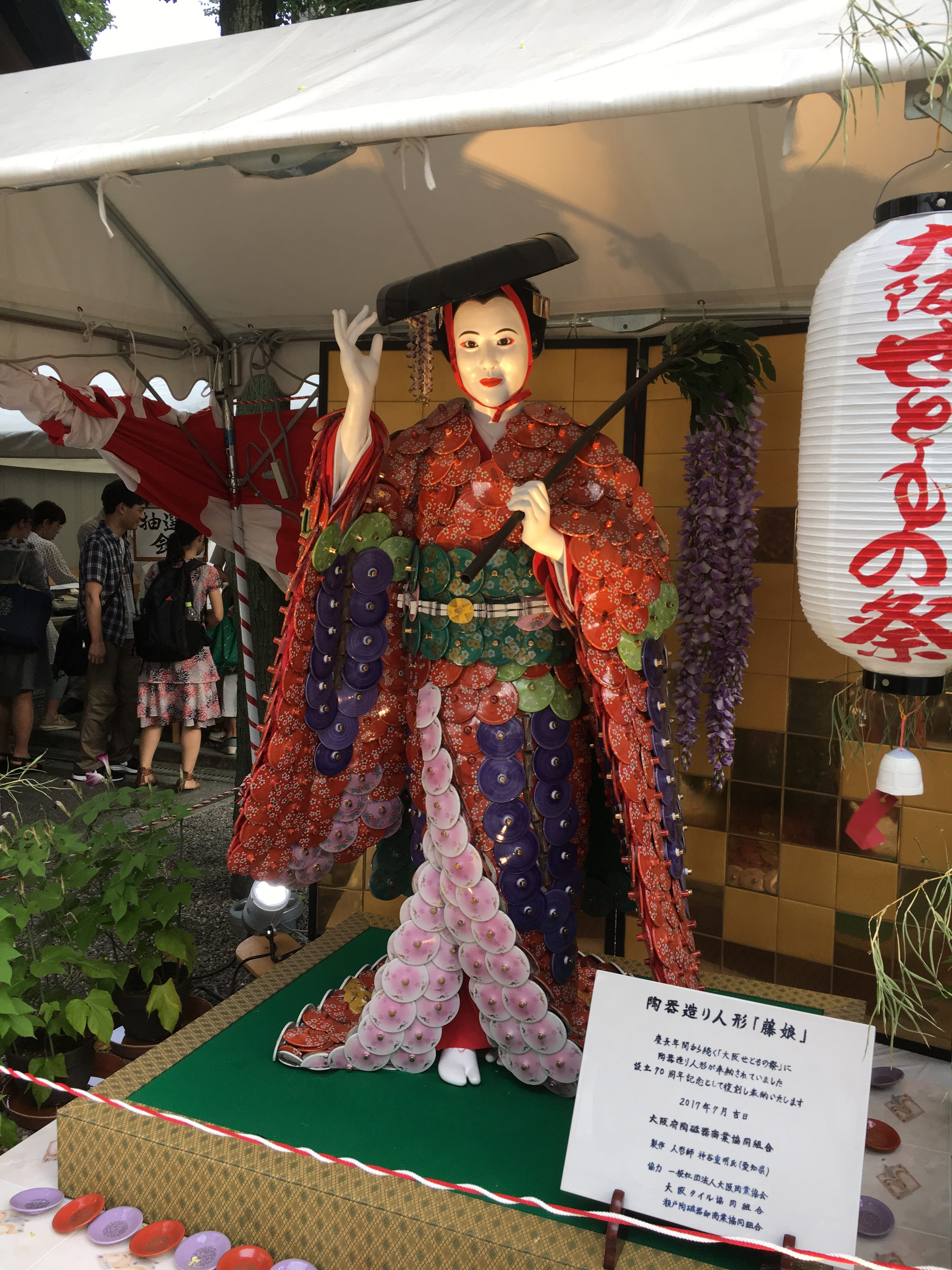 life-size porcelain doll of a japanese lady in traditional clothes with wisteria branch