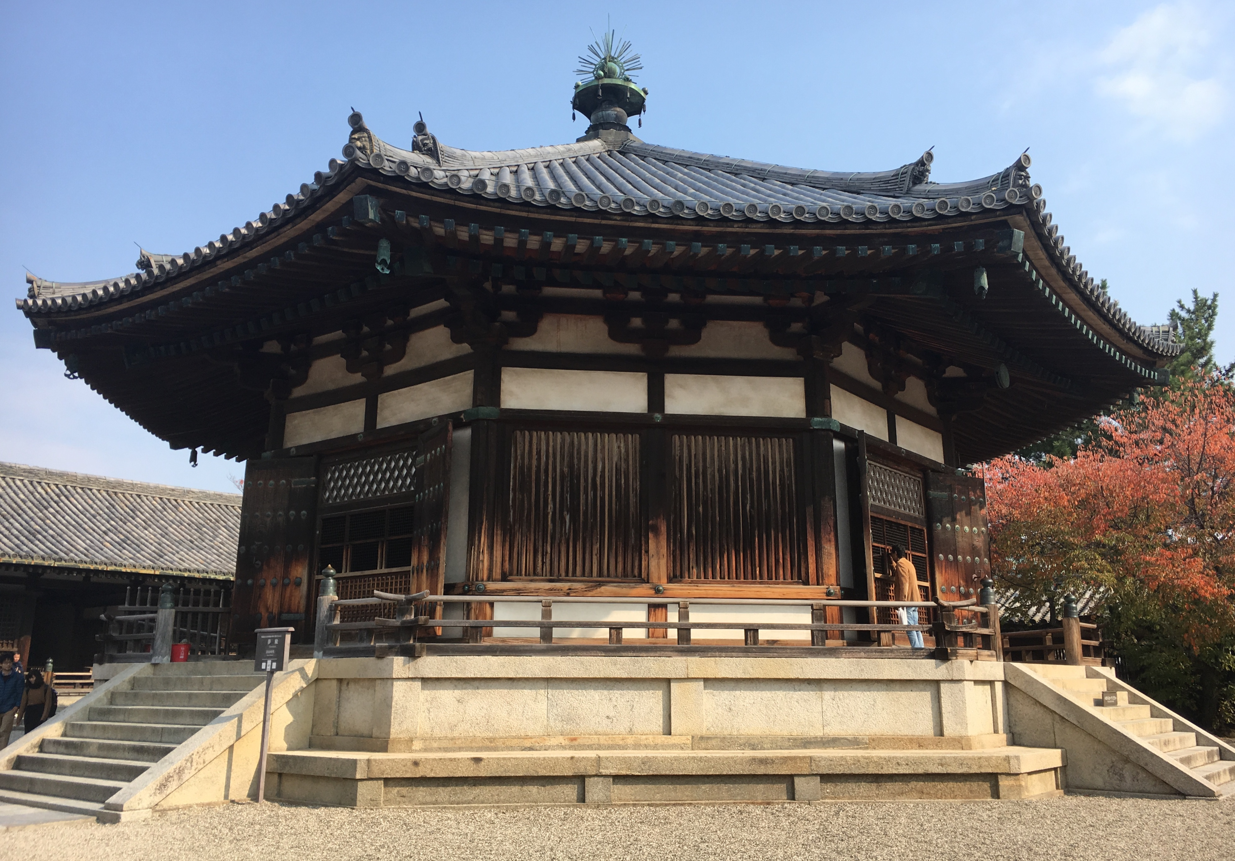 octagon shaped yumedono building in Horyu-ji temple surrounded by bright red leaves