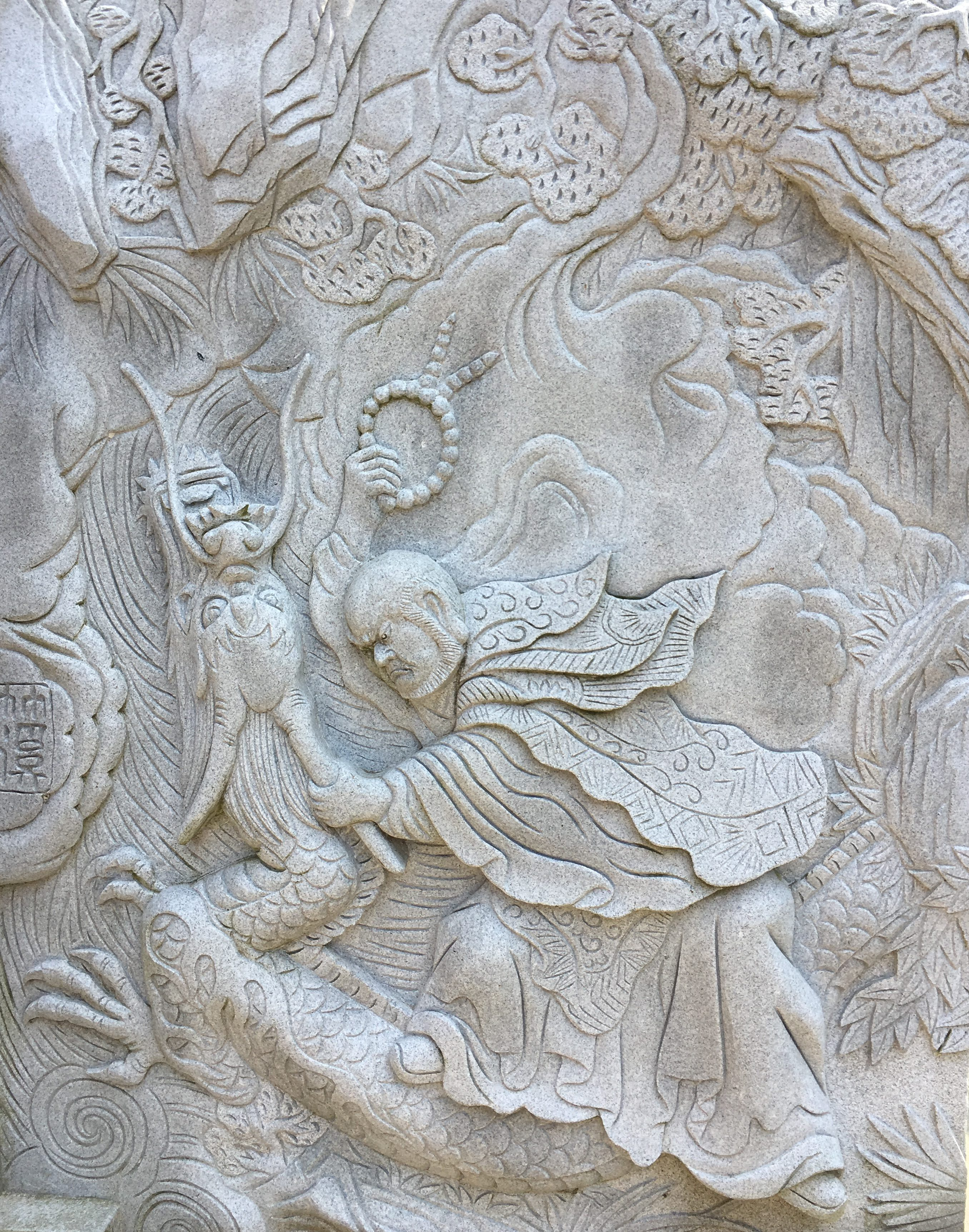stone carving at oka-dera temple of monk gien battling a ferocious dragon