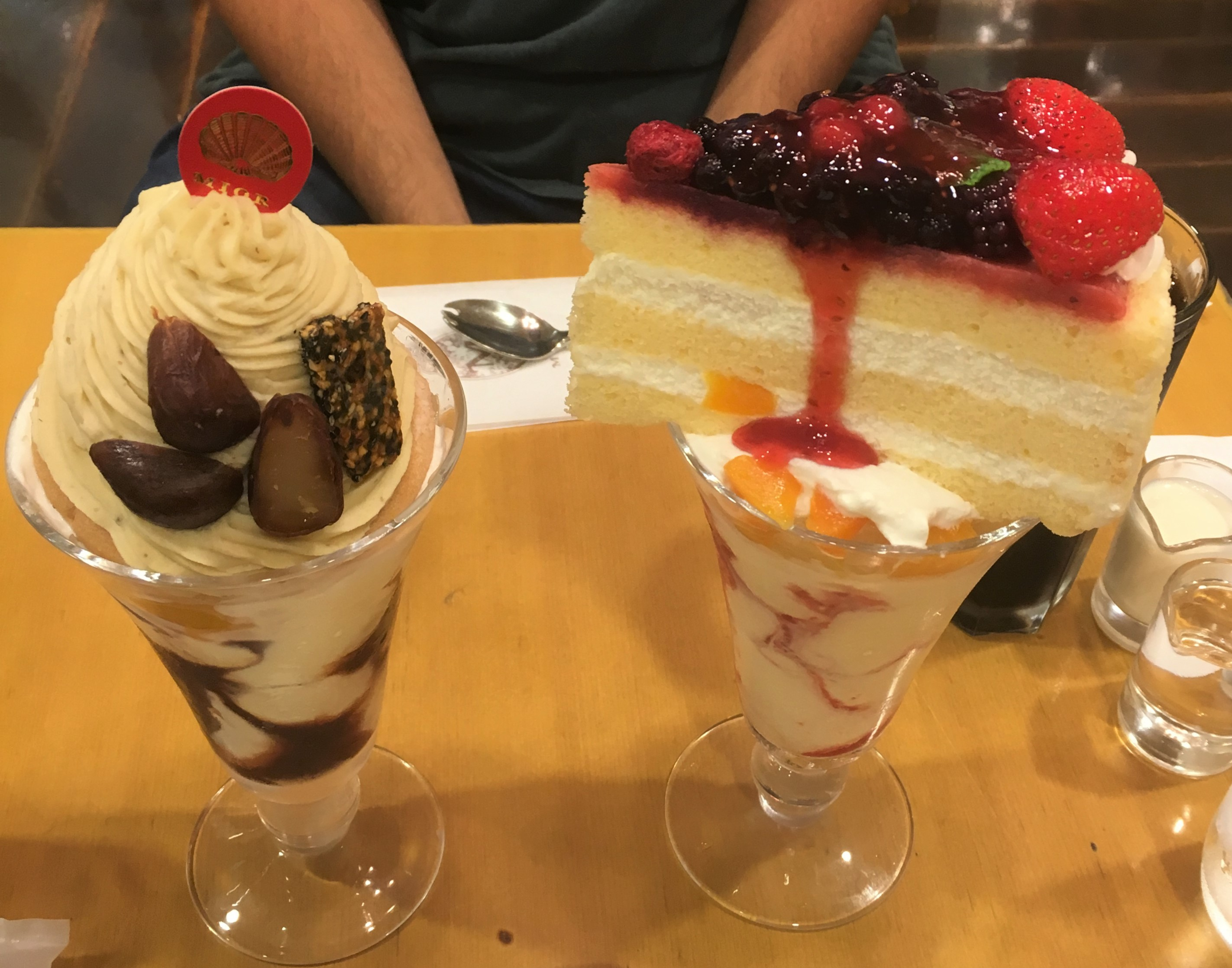 large ice cream parfaits topped with while slices of different kinds of cake