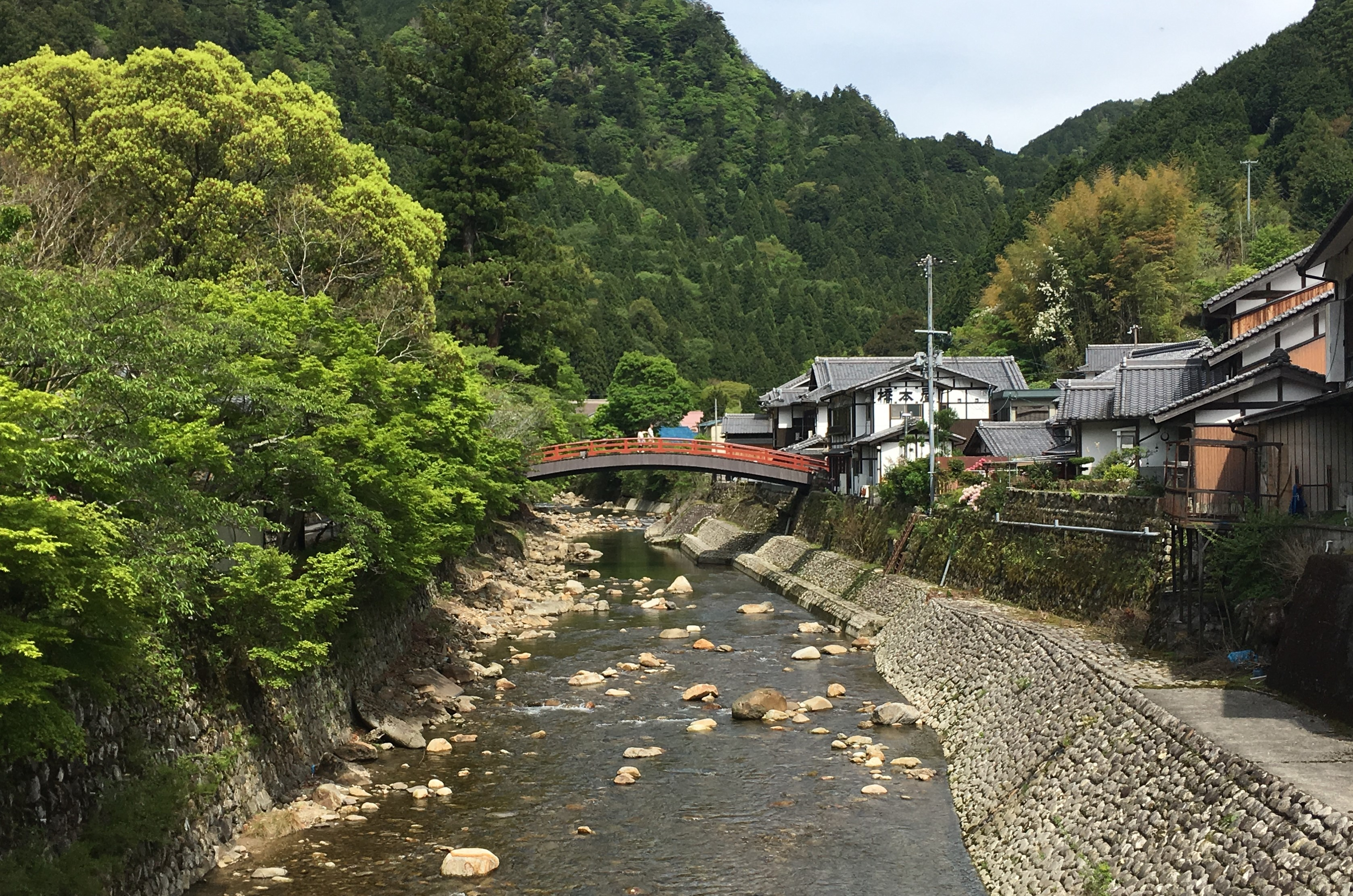 bright red taiki bashi over a rocky river leading to muro-ji temple