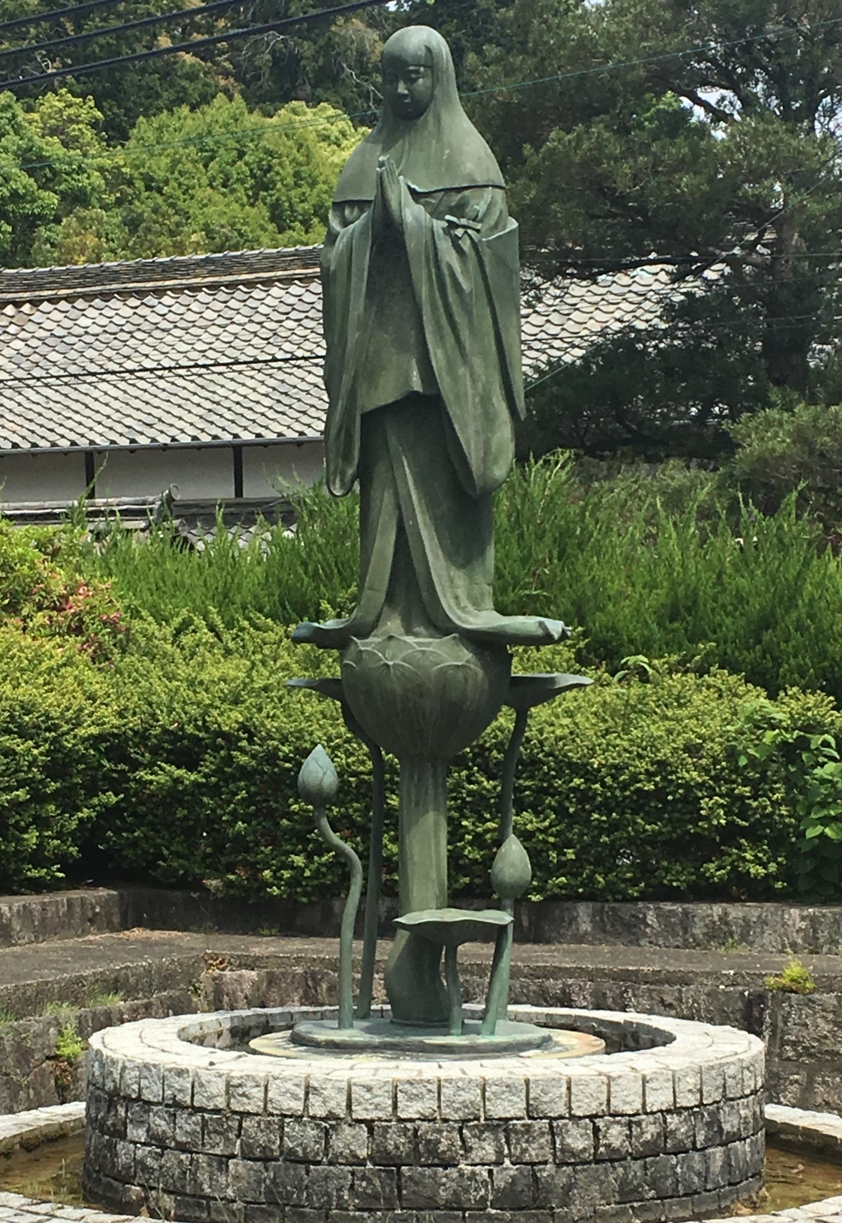 Green statue of princess chujo on a lotus at Taima-dera Temple in Nara