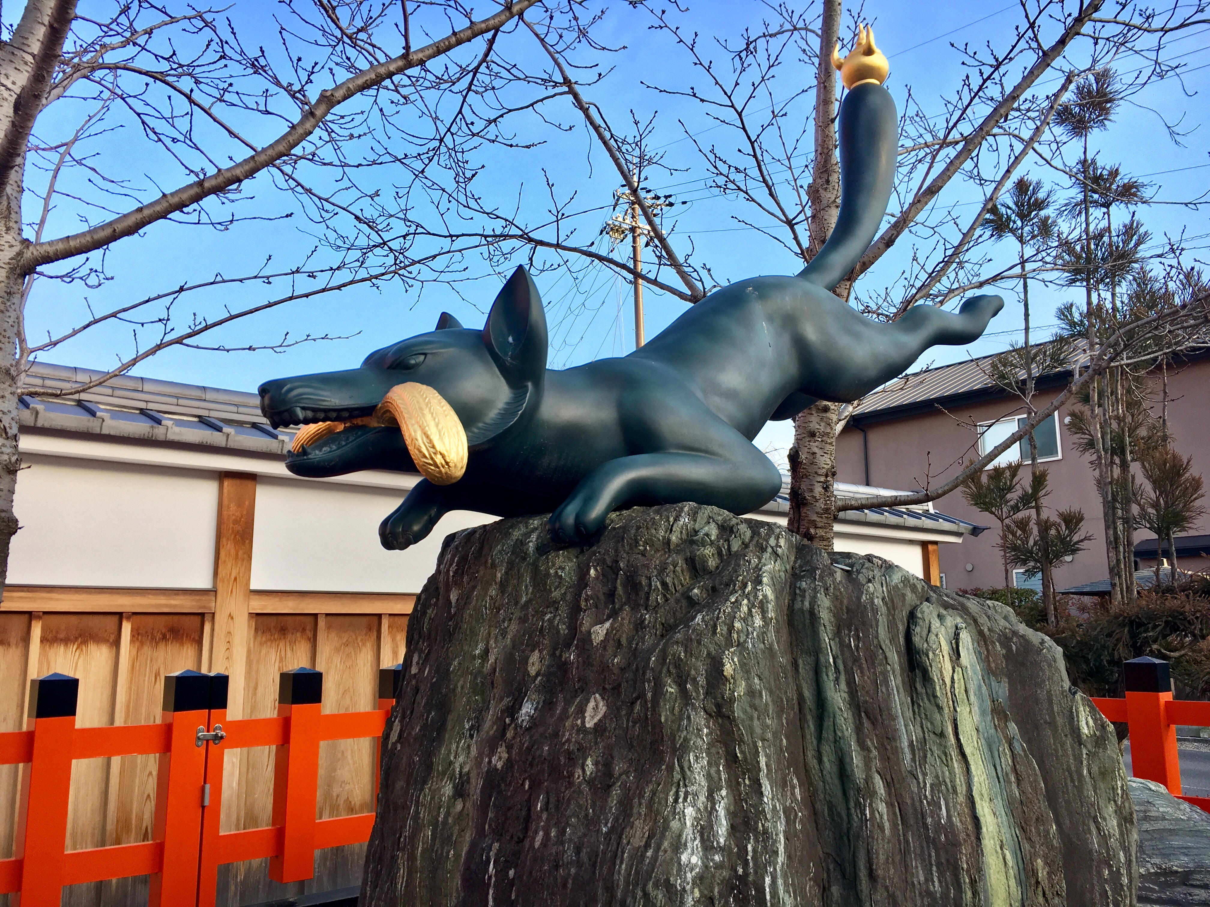 statue of a fox holding a bundle of rice