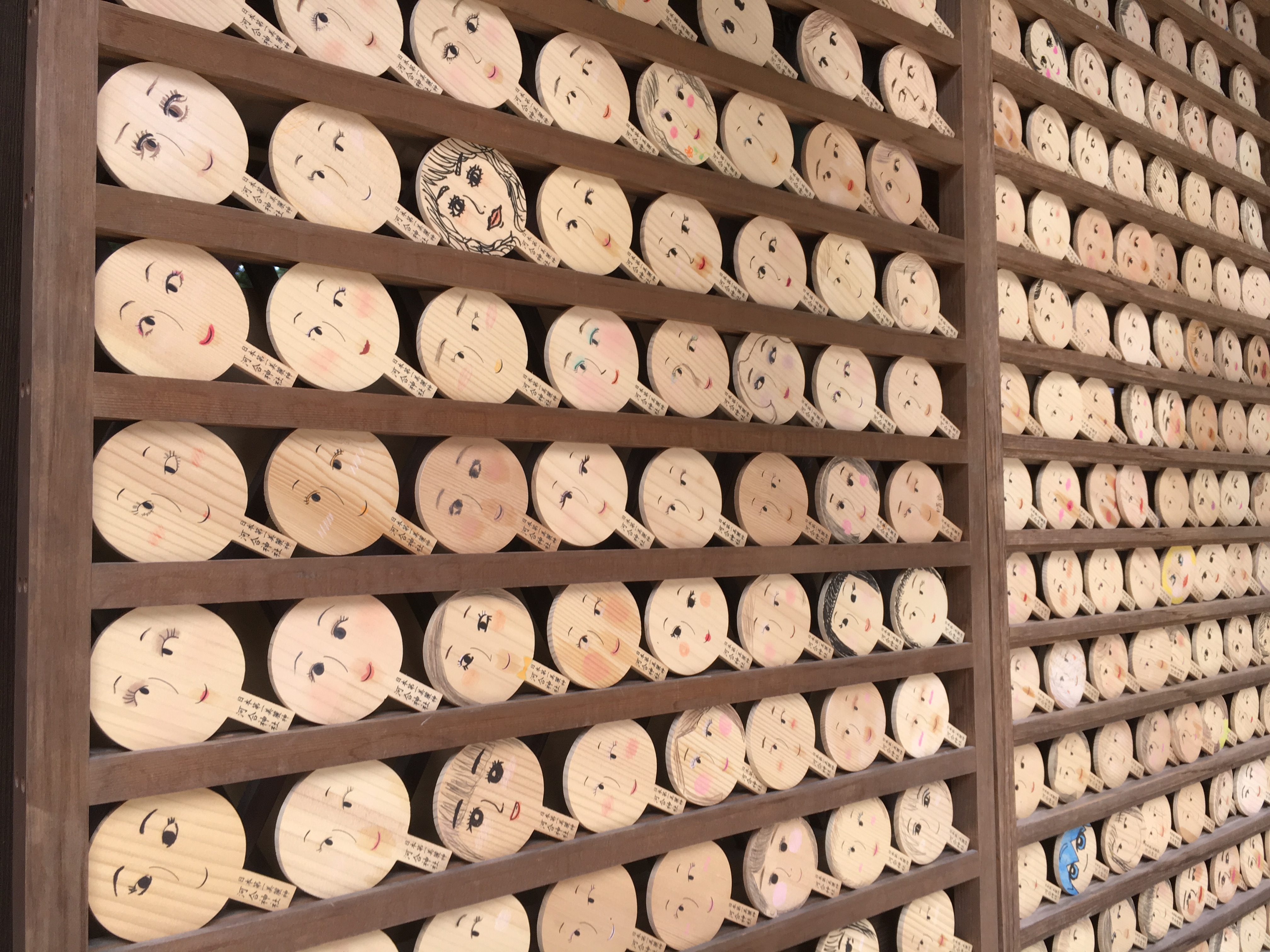 mirror shaped ema at kawai shrine with beautiful faces drawn on them.