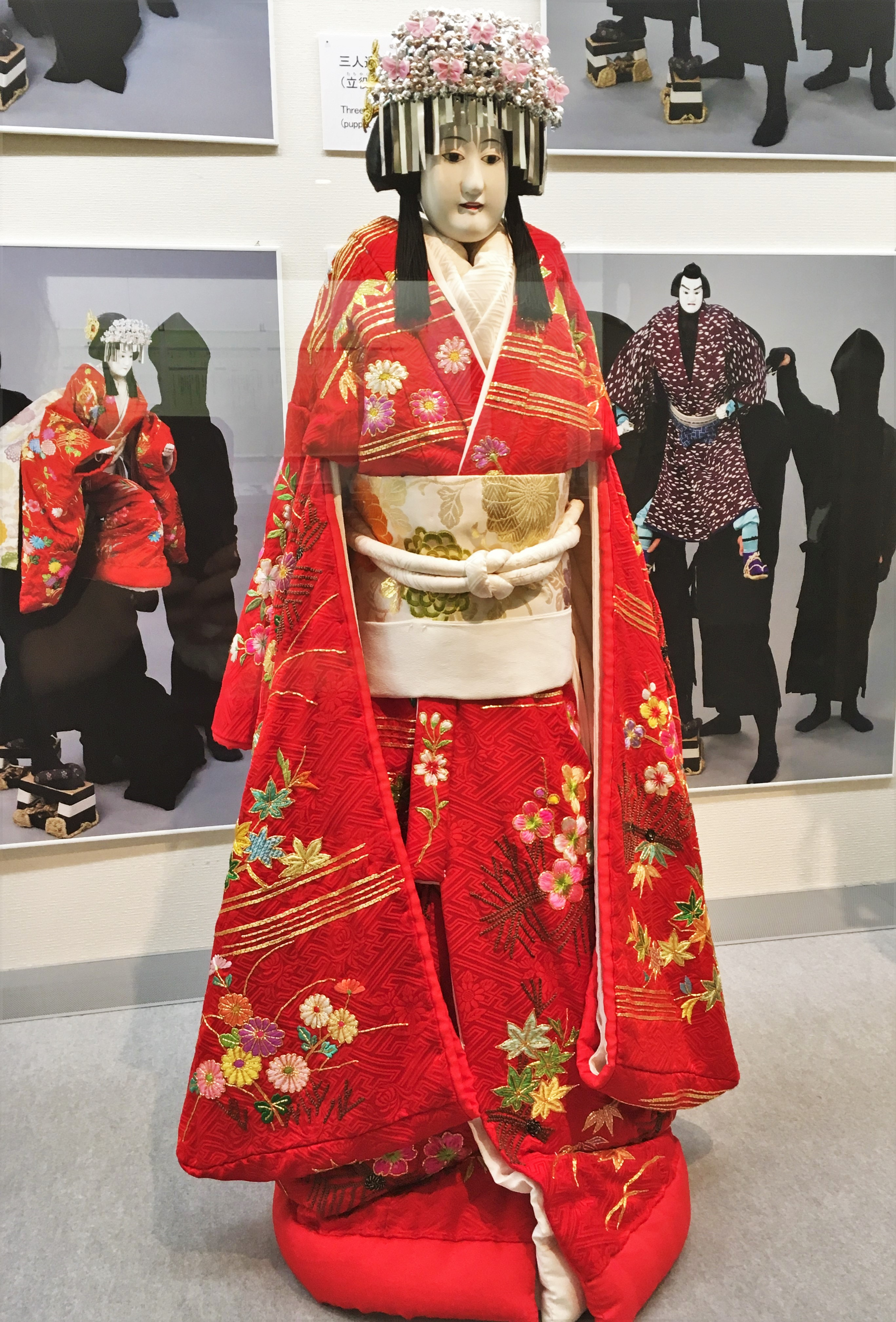 bunraku puppet dressed in a chrerry blossom and silver head dress and a red kimono